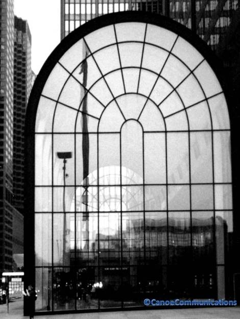 glass and steel hall surrounded by skyscrapers