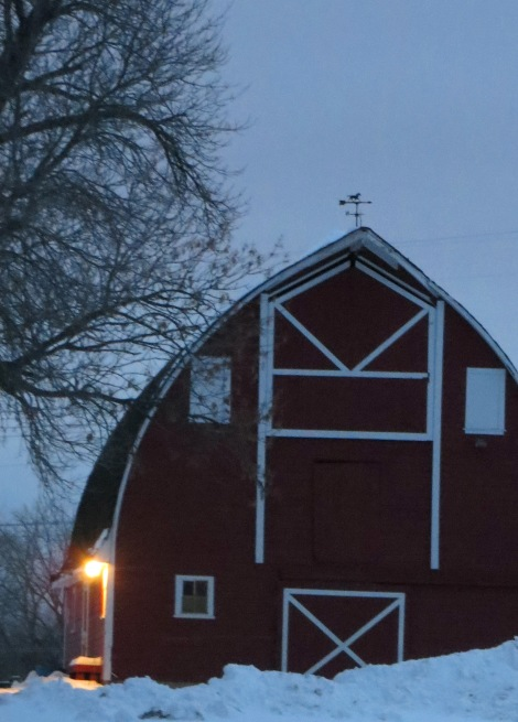 a light shines bright on a old red barn on a winter night